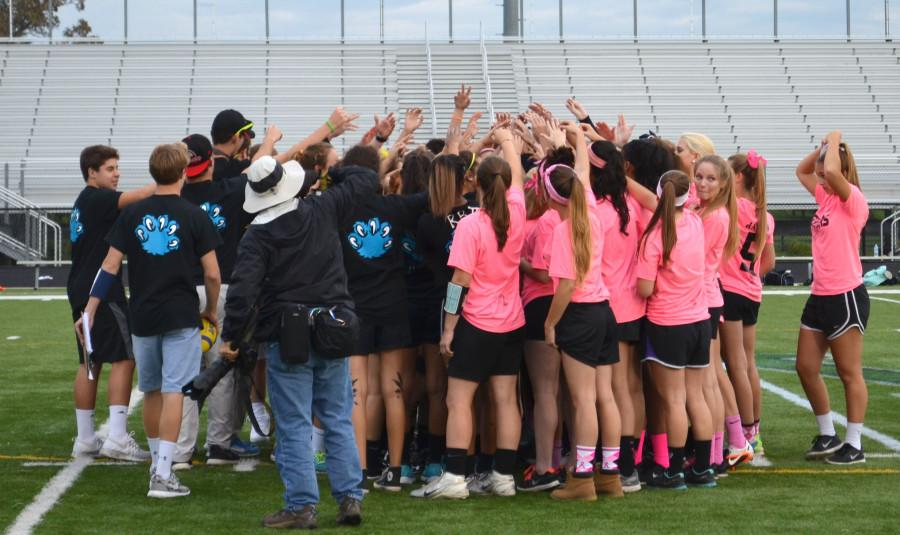 The+senior+and+junior+powderpuff+teams+gather+together+and+cheer+themselves+on+before+the+game+starts.