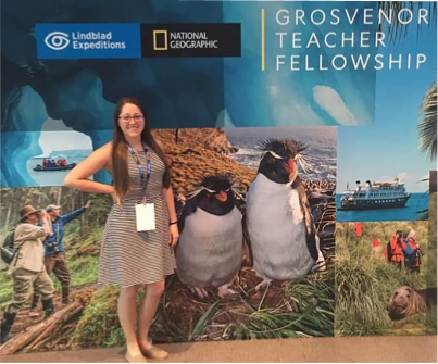 Ms. Schafer poses in front of the Grosvenor Teacher Fellowship sign. Photo provided by Stephen McClanahan